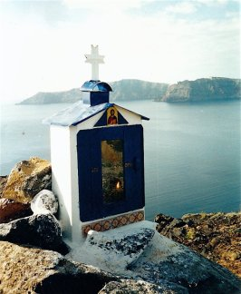 I constructed the shrine out of tin, glass and ceramic tiles and painted it. Inside there's an alter made of volcanic rocks, an icon of the Old Testament Archangel Uriel, an oil lamp, matches, olive oil, personal keepsakes. It is cemented to a boulder at cliff edge. The caldera is in the distance. The sea below me is very deep almost bottomless, the crater created by the eruption.