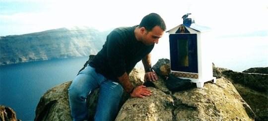 December 2000, building my shrine overlooking the caldera of an ancient volcano. Location: outside Oia village, on a remote hiking trail northern tip of Santorini Island.