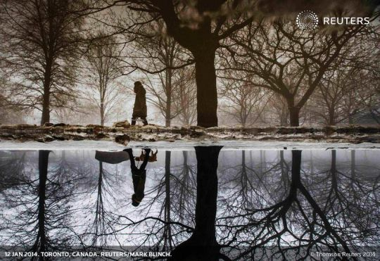 A woman is reflected in a puddle from rain and melted ice as she walks her dog in Toronto